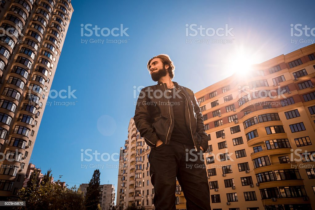 Bearded young man standing among modern buildings. stock photo