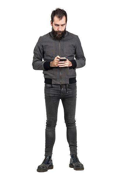Jovem barbudo punk digitando a mensagem no seu celular - foto de acervo