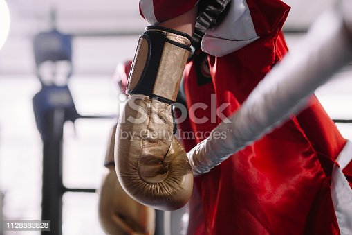 521301688 istock photo beaten boxer in yellow boxing gloves leaning on ropes 1128883828