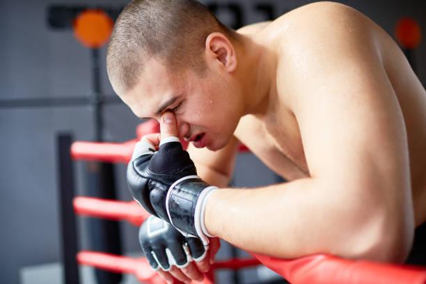 beaten boxer leaning on ring railing - head injury stock photos and pictures