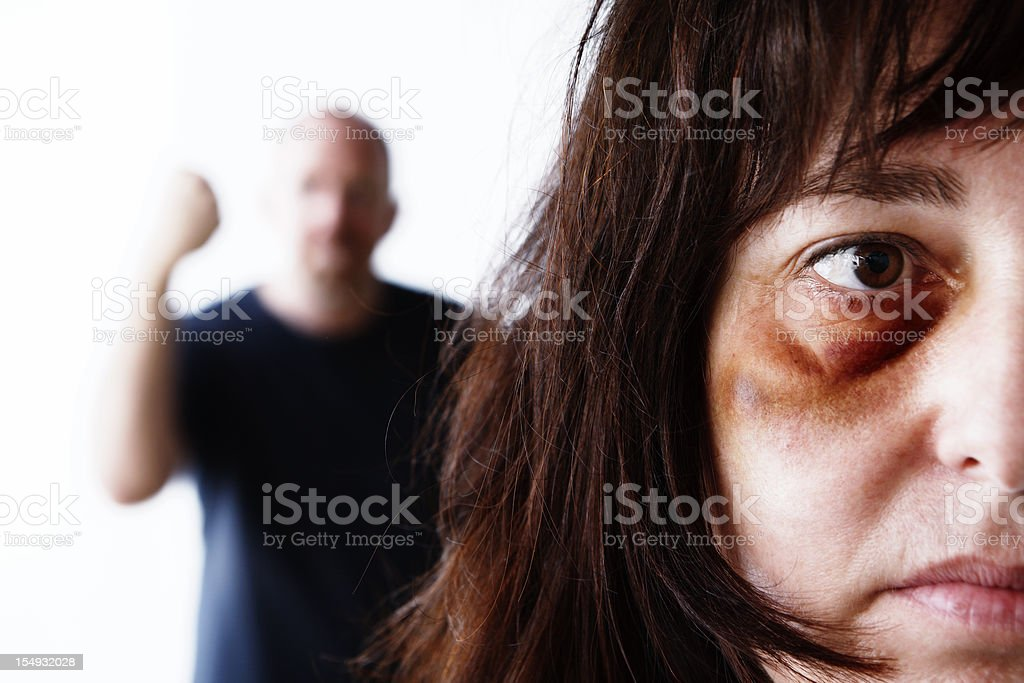 Beaten, desperate woman with man shaking fist behind her, threateningly stock photo