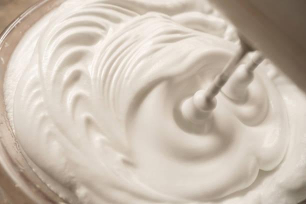 Beaten egg white with the blender stock photo