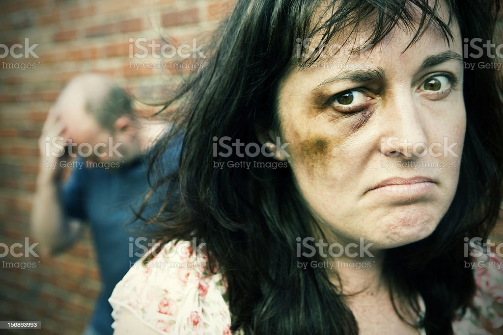 Beaten woman looks defiant stock photo