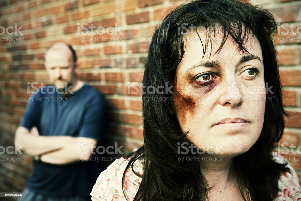 Beaten woman tries to leave threatening man in background stock photo
