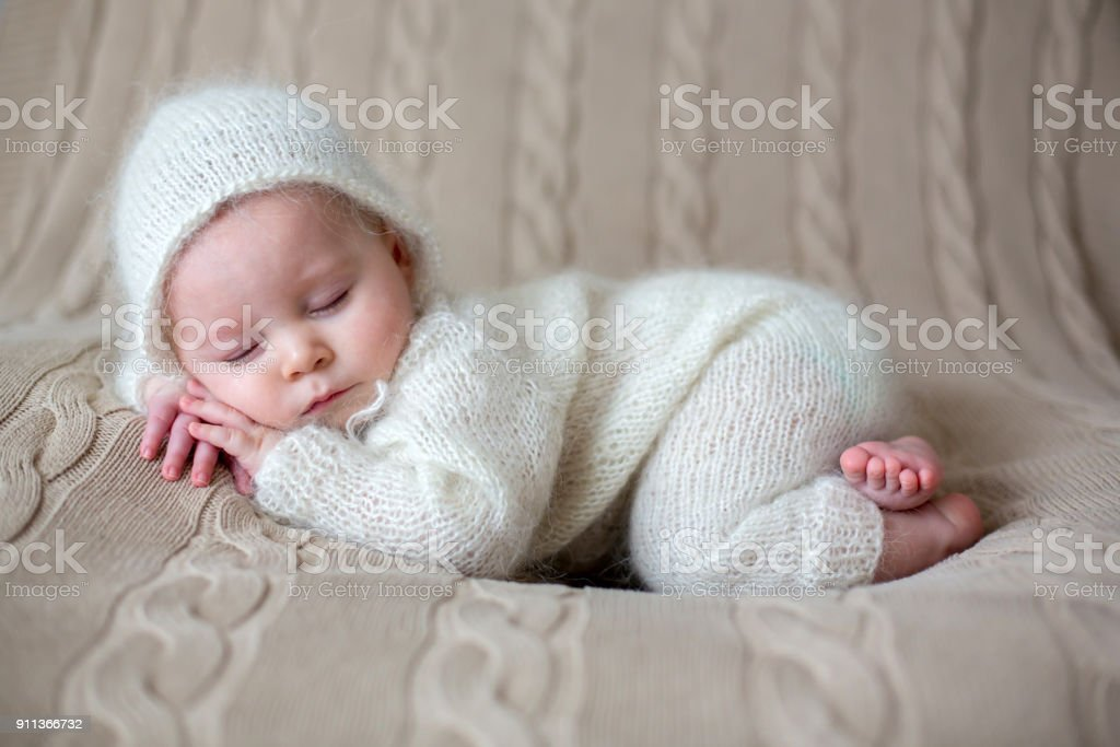Beatiful baby boy in white knitted cloths and hat, sleeping stock photo