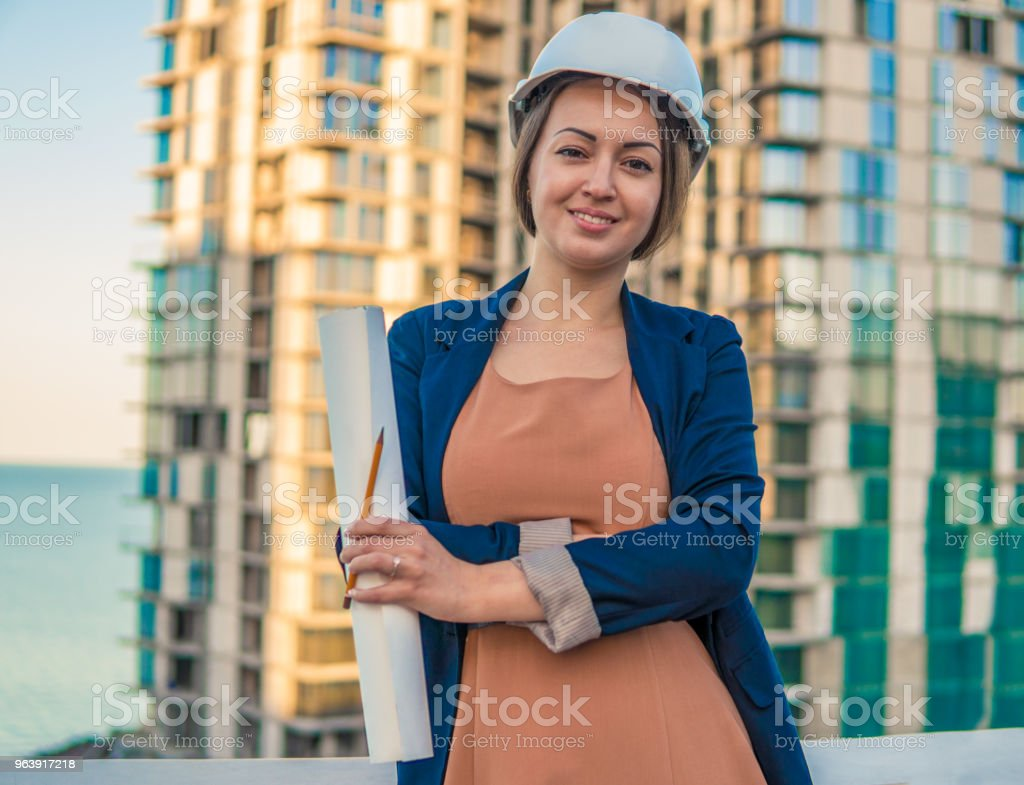 beatiful business woman engineer is standing with plan papers. - Royalty-free Adult Stock Photo
