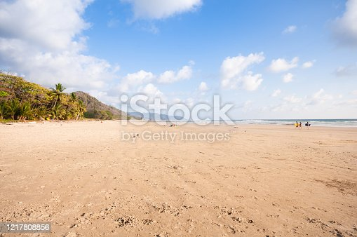 Photography of a beautiful beach in northern Costa Rica (Pavones), close to the border of Panama. In the front a small wooden shack built of palm tree leaves to spend some shade.\nThree tourists with bodyboards coming out of the water in the far background.