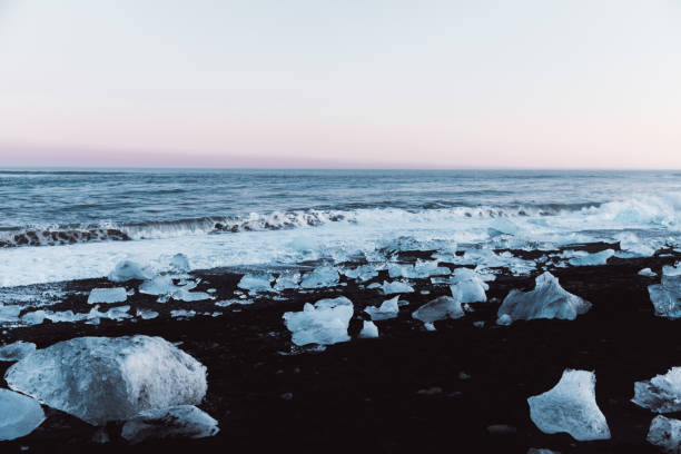 Beauicul black sand beach with pieces of icebergs during winter sunset in Iceland stock photo