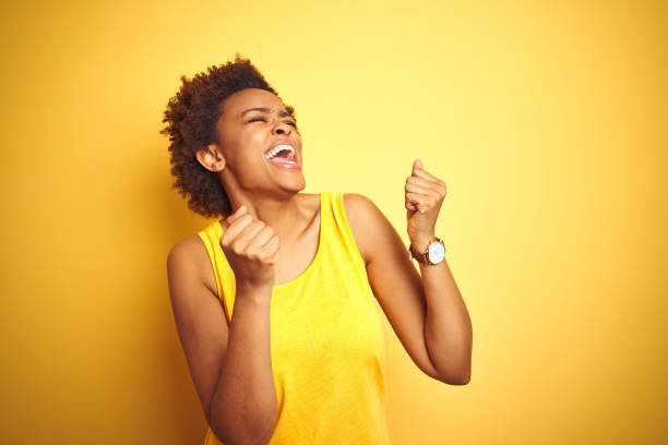 Beauitul african american woman wearing summer t-shirt over isolated yellow background very happy and excited doing winner gesture with arms raised, smiling and screaming for success. Celebration concept. stock photo