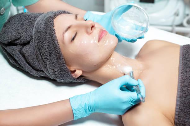 kosmetikerin wendet gesichtsmaske mit pinsel auf schöne junge frau im spa-salon. kosmetische verfahren hautpflege. - peeling bürste stock-fotos und bilder