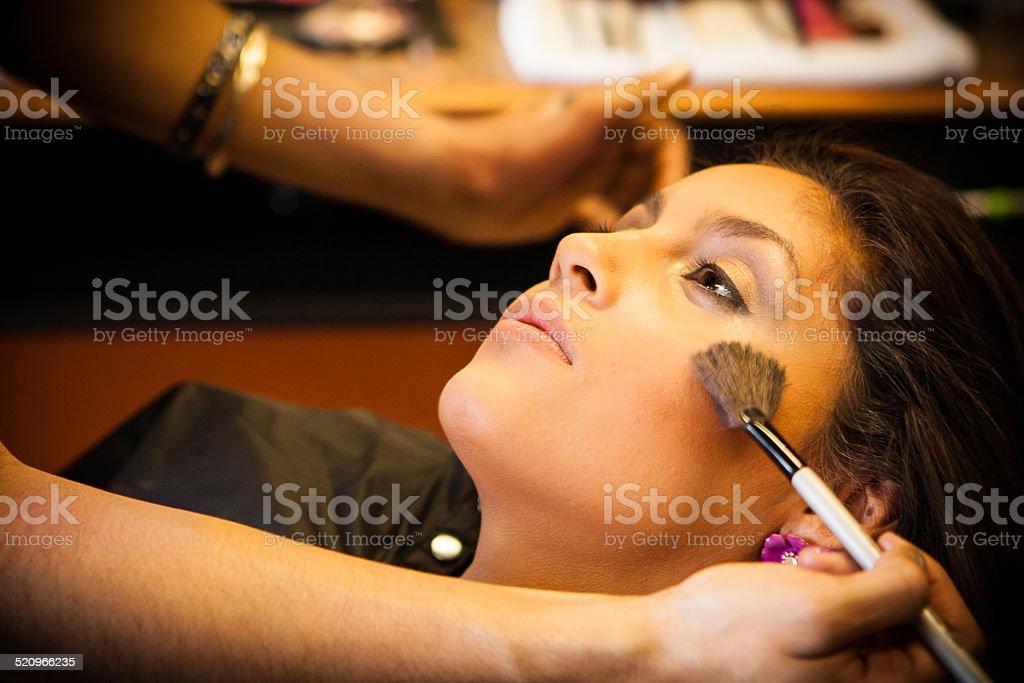 Beautician applies make up to a pretty, beautiful Latino Customer. stock photo