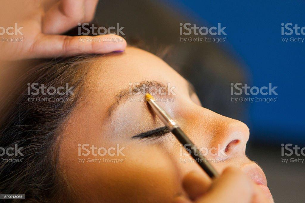Beautician applies make up to pretty Latino Customer stock photo