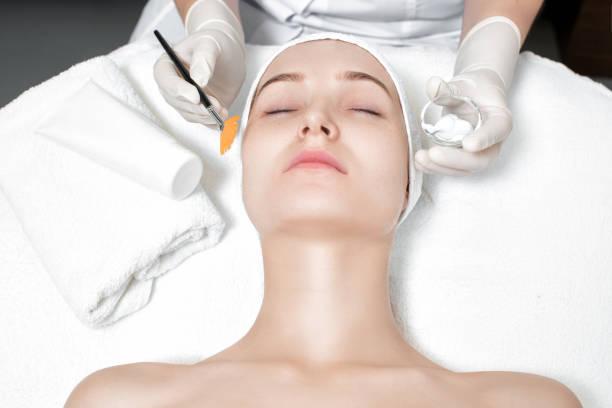 esthéticienne applique le masque sur le visage de femme - Photo