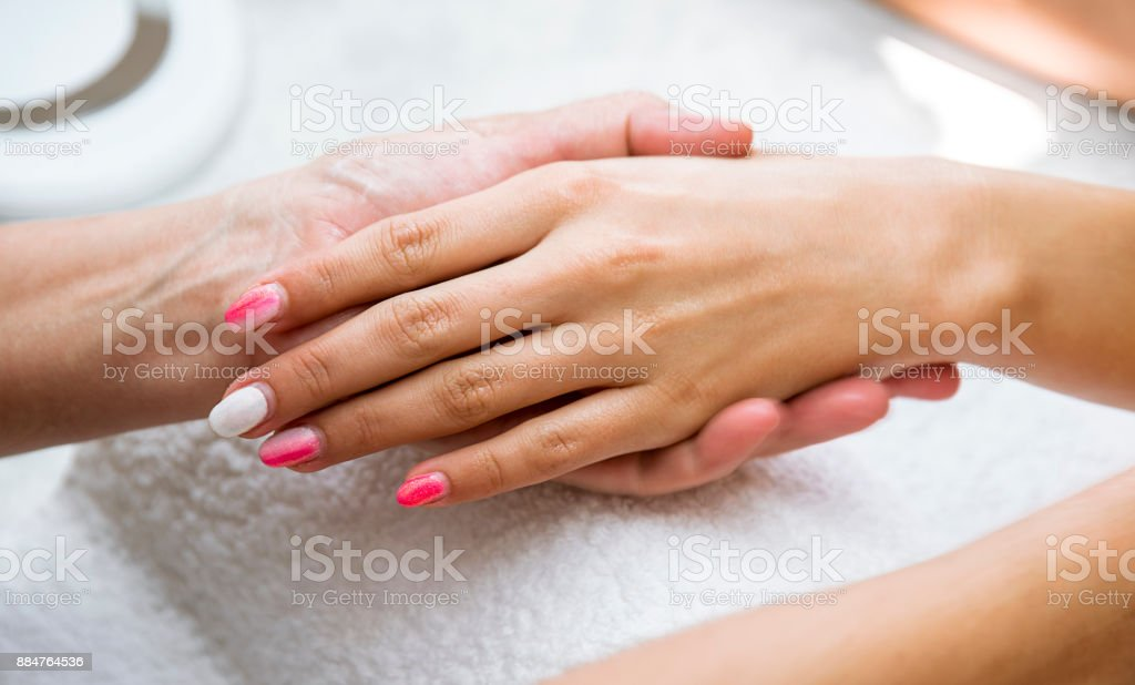 Beautician applying red varnish to finger nails. stock photo