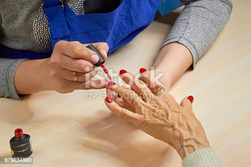 istock Beautician applying red varnish to woman nails. 979634990