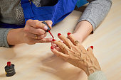 Beautician applying red varnish to woman nails.