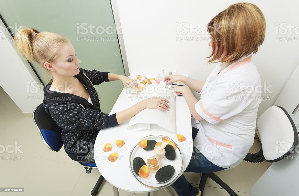 Beautician cleaning cuticles hands female client. Beauty salon. royalty-free stock photo