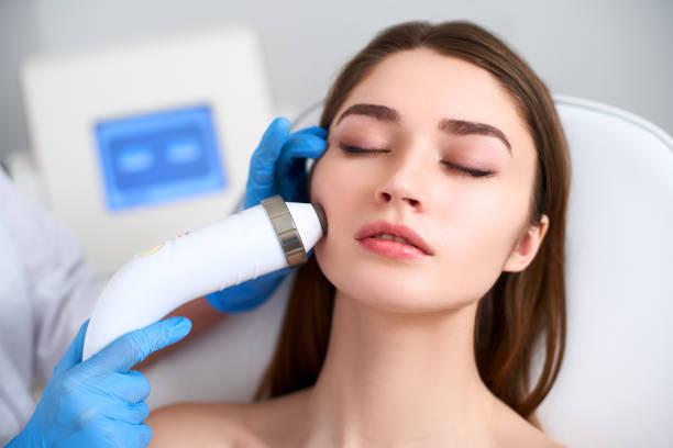 美容師医師は美容室に敷設完璧な女性の顔のための rf リフティング手順を行います。ハードウェアの美容。電気顔面マッサージを受ける患者。皮膚の若返りとしわの平滑化 ストックフォト