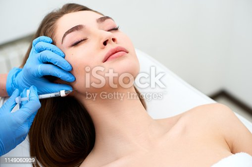 istock Beautician doctor with filler syringe making injection to jowls. Masseter lines reduction and face contouring therapy. Anti-aging treatment and face lift in cosmetology clinic. Patient lying on chair 1149060939