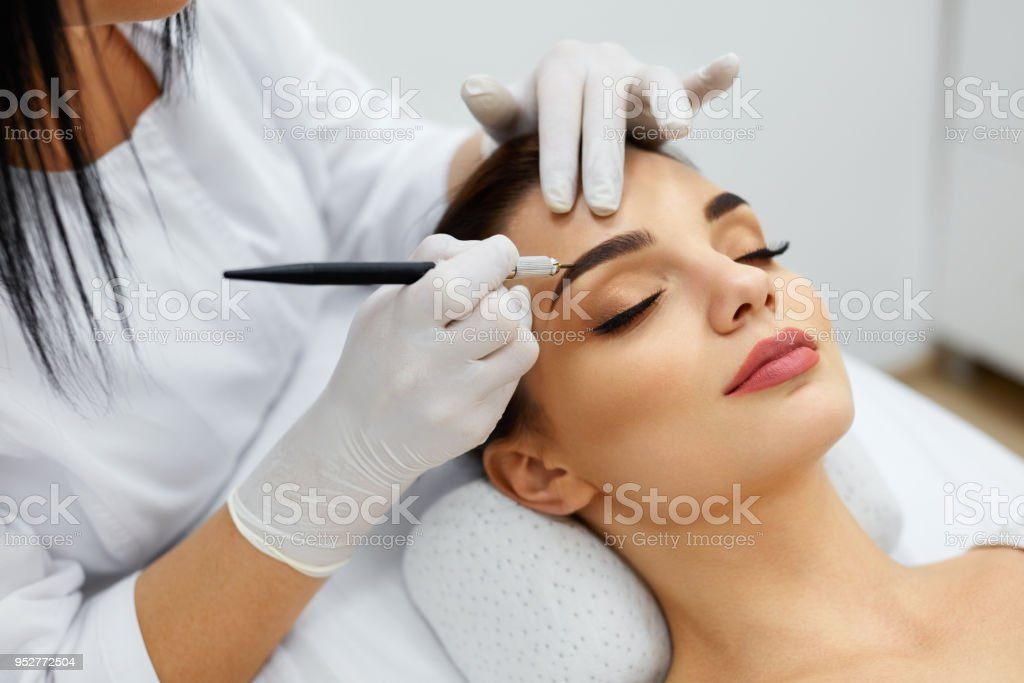 Beautician Doing Permanent Eyebrows Makeup Tattoo On Woman Face stock photo