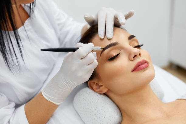 beautician doing permanent eyebrows makeup tattoo on woman face - beauty treatment stock photos and pictures