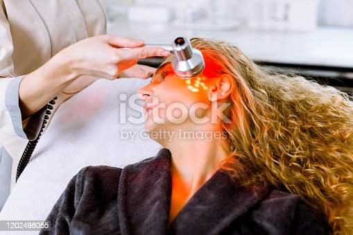 istock beautician doing red led light therapy to blond woman in beauty salon, facial photo therapy for skin pore cleansing. Anti-aging treatments and photo rejuvenation procedure, close up 1202498055