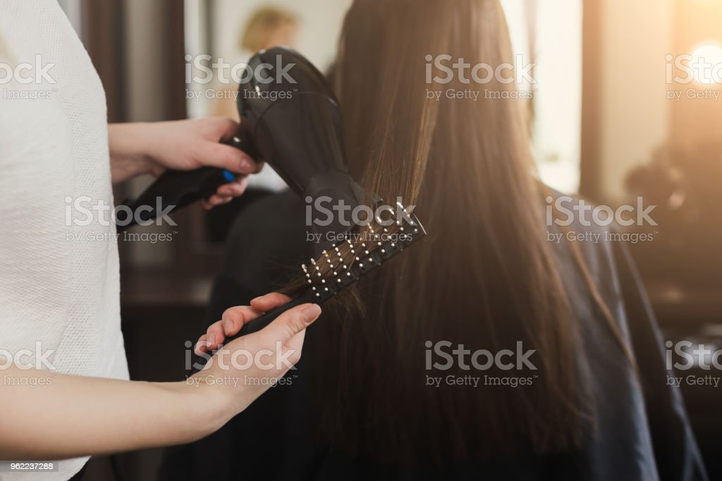 Beautician drying woman's hair stock photo