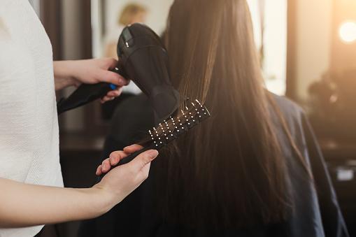 美容師乾燥婦女的頭髮 照片檔及更多 20多歲 照片