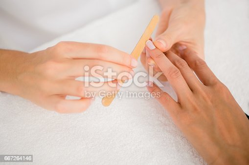 istock Beautician filing female clients nails at spa beauty salon 667264146