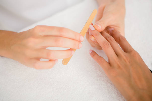 Beautician filing female clients nails at spa beauty salon stock photo