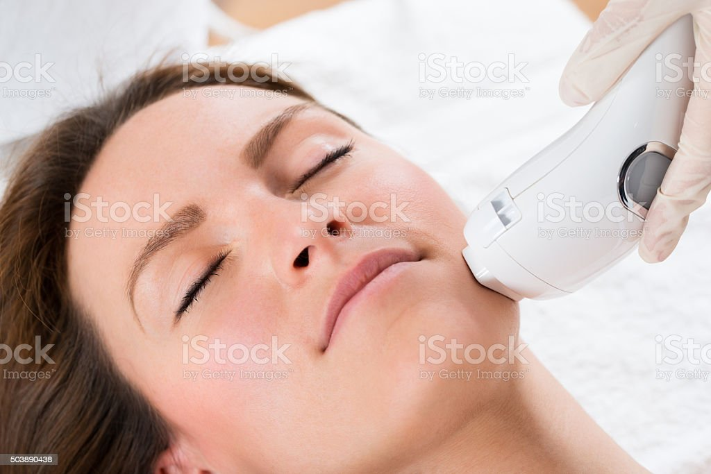 Beautician Giving Laser Epilation Treatment To Woman Face stock photo