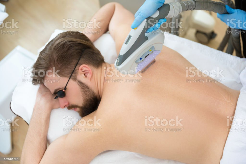 Beautician giving men laser epilation stock photo
