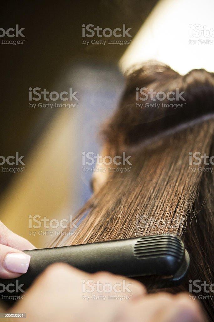 Beautician, Hair Dresser uses Hair Straightener on Customer's Hair stock photo