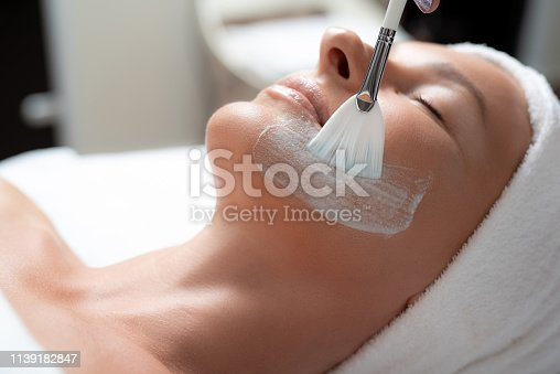 Relaxing at spa. Close up portrait of beautiful middle aged woman with cosmetic clay on her cheek and chin. She is lying on massage table with closed eyes and soft towel on head
