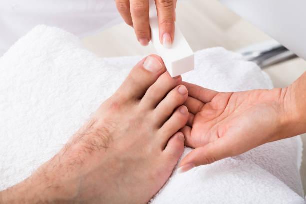 kosmetikerin hand feilen der nägel - fußpflege stock-fotos und bilder