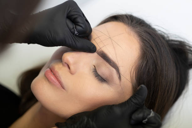Beautician in the saloon doing the perfect architecture of eyebrows. Beautician is doing a ideal shape of eyebrows with thread. threading stock pictures, royalty-free photos & images
