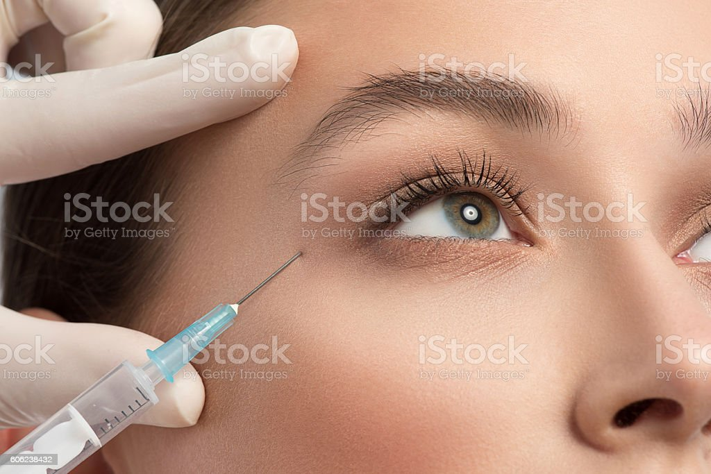 Beautician injecting liquid into human skin stock photo