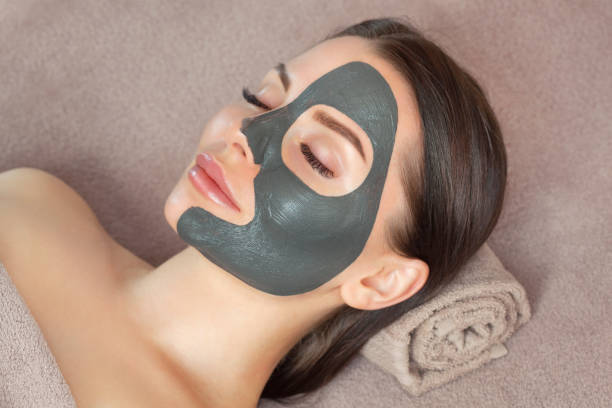 Beautician makes a black clay mask to rejuvenate the skin to beautiful woman.Cosmetology concept and treatment of problem skin. stock photo