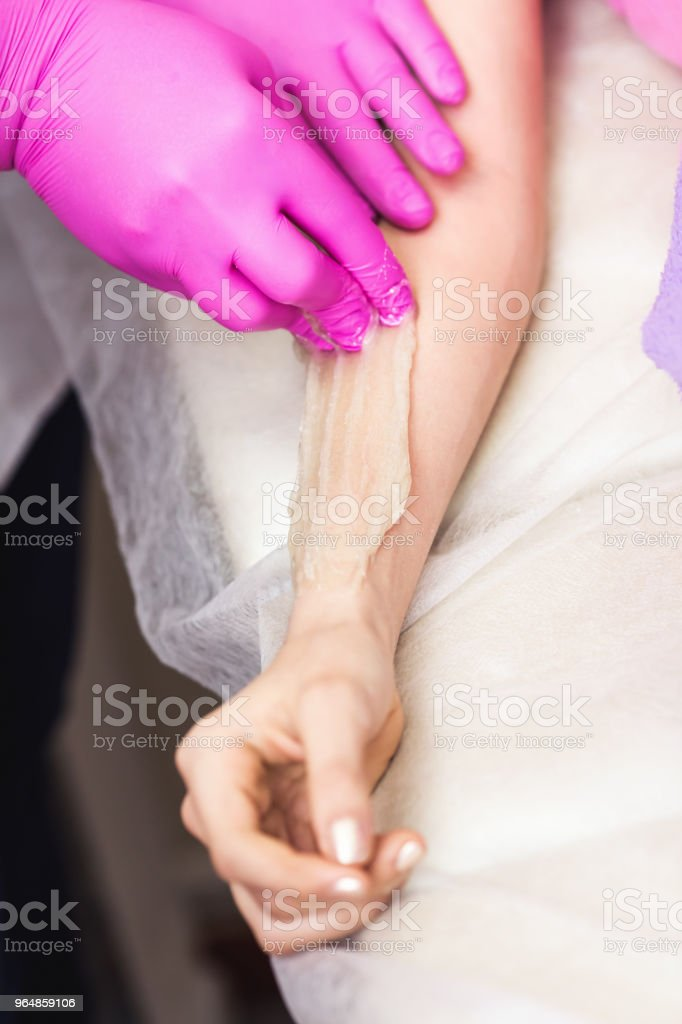 Beautician makes epilation close-up girl on her hand. Shugaring. royalty-free stock photo