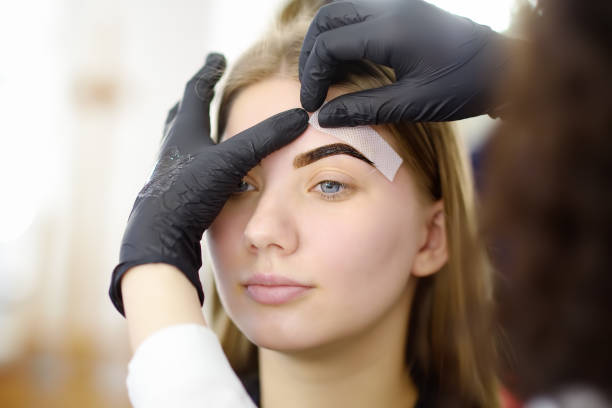 Beautician making depilation with wax strip young woman's eyebrows in spa center. stock photo