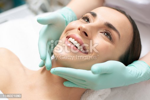 Close up photo of the face of smiling woman and hands in green rubber gloves touching it gently
