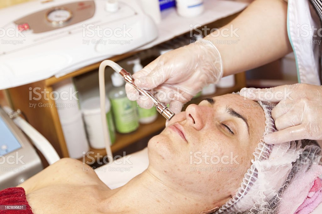 Beautician performs dermabrasion treatment on her face. stock photo
