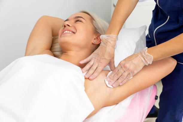 beautician prepares hair removal underarms stock photo