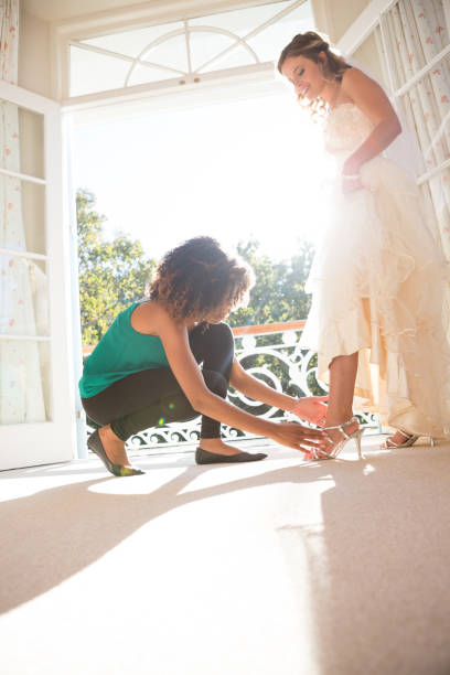 kosmetikerin auf sandalen braut zu hause - hochzeitskleid in schwarz stock-fotos und bilder