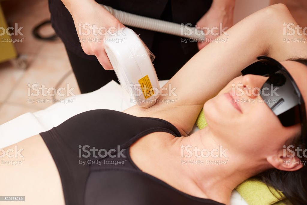 Beautician Removing Hair Of Young Woman with laser stock photo