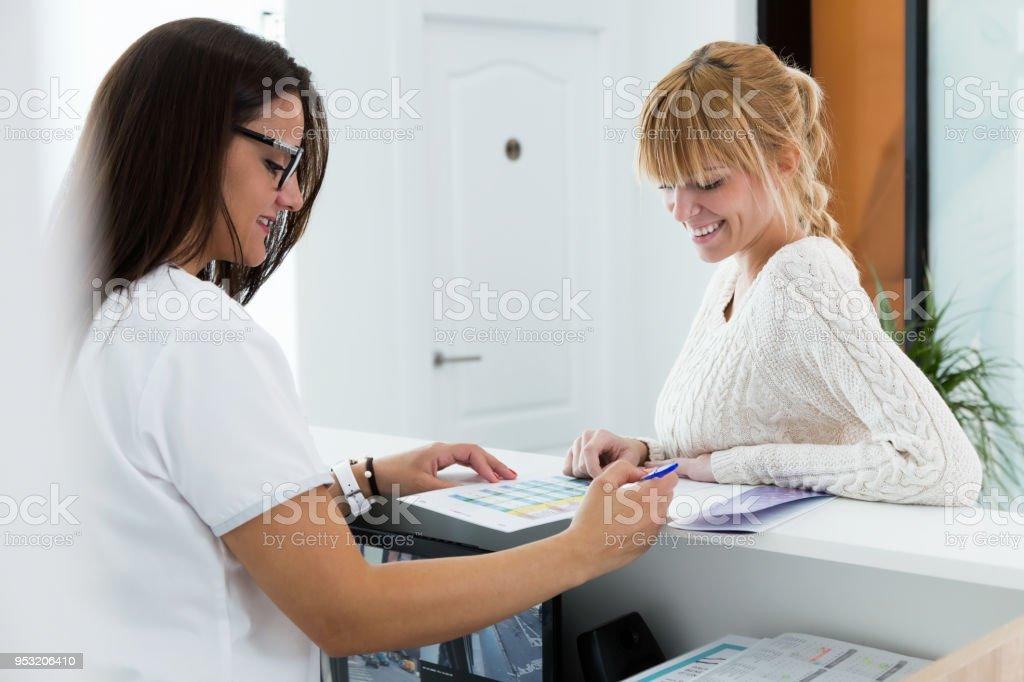 Kosmetikerin zeigen die Preise ihrer Dienstleistungen zu einem weiblichen Kunden an der Rezeption der Klinik. – Foto