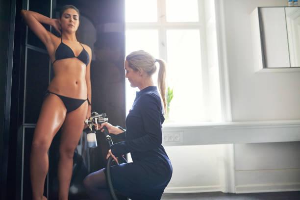 Beautician spraying tan bodypaint on woman in salon stock photo
