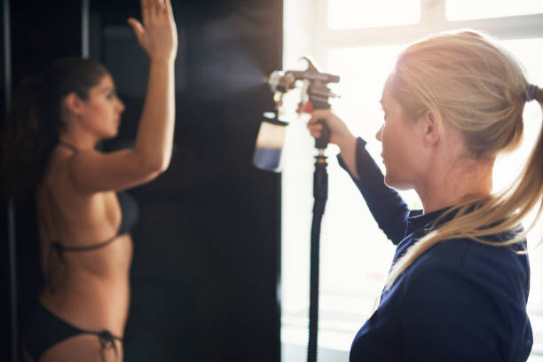 Beautician spraying tan on woman in salon Cosmetologist using airbrush for spray tan apply to young woman hand in beauty salon. airbrush stock pictures, royalty-free photos & images