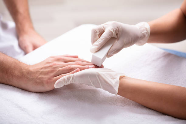 Beautician Taking Care Of Man's Nail Close-up Of Beautician Manicure Nail Buff Of Man In Spa pedicure manicure men beauty spa stock pictures, royalty-free photos & images