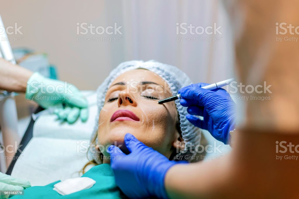 Beautician touch and draw correction lines on woman face stock photo
